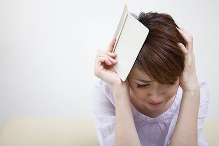 passbook: Middle women who suffer from head to look at the passbook Stock Photo