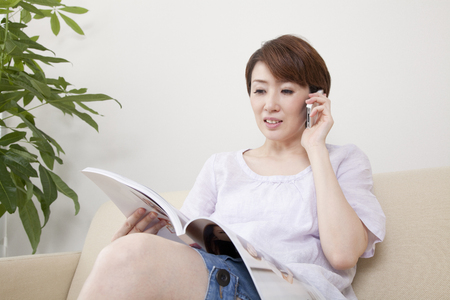 multi family house: Women who phone while watching the magazine