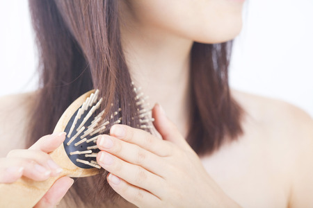 Woman combing her hair with a brush Фото со стока