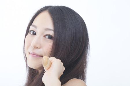 ブラシで髪を梳く女 写真素材