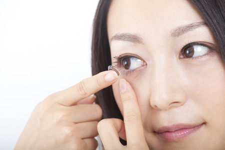 Women put a contact lens in the eye Stock Photo