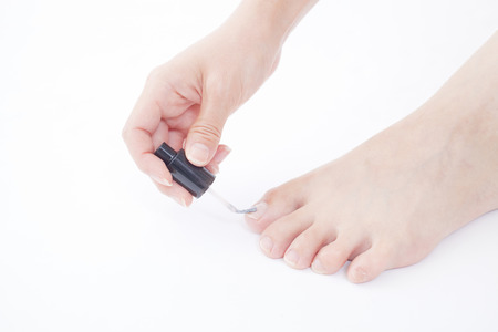 healing with sound: Hand of a woman painting the nail on the foot