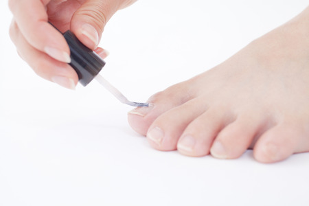 nailcare: Hand of a woman painting the nail on the foot