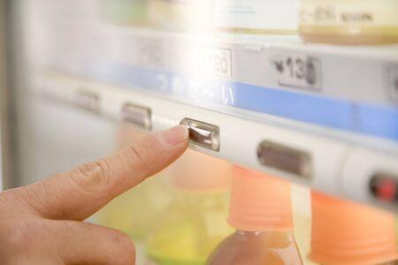 自販機で飲み物を買う人