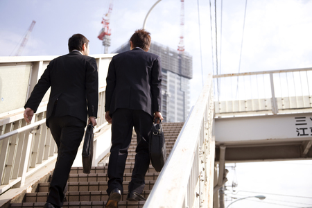 Footbridge: Businessman climb the footbridge Stock Photo