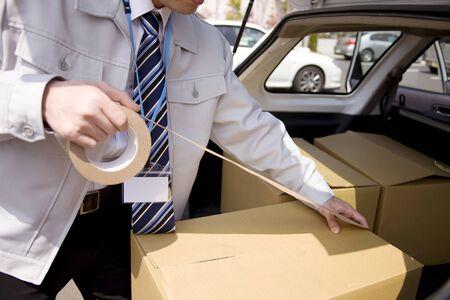 deliverables: Businessman put the duct tape on cardboard
