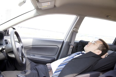 Businessman taking a nap in the car