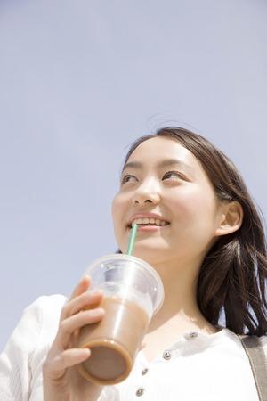 iced coffee: Woman walking while drinking iced coffee