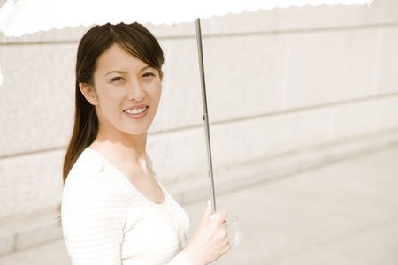 refers: Woman walking in the city refers to the parasol Stock Photo