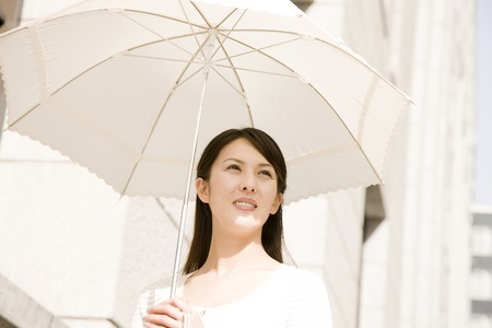 Woman walking in the city refers to the parasol 版權商用圖片