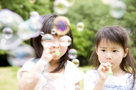 kindergartener: Two girls playing with soap bubbles Stock Photo