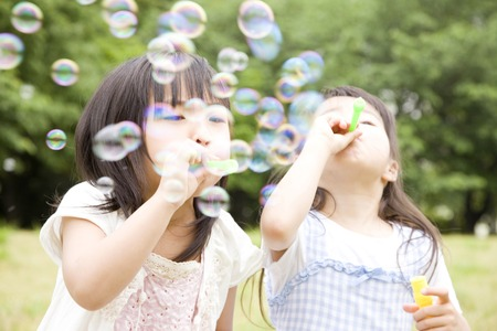 Two girls playing with soap bubbles Stock Photo