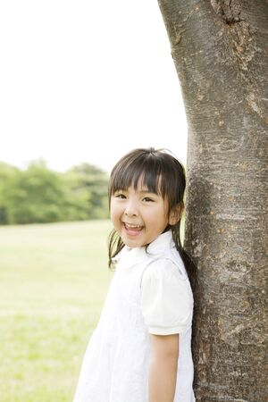 kindergartener: Girl smile leaning on a tree Stock Photo