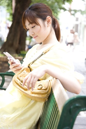 通信: Women to email on the phone sitting on a bench 写真素材