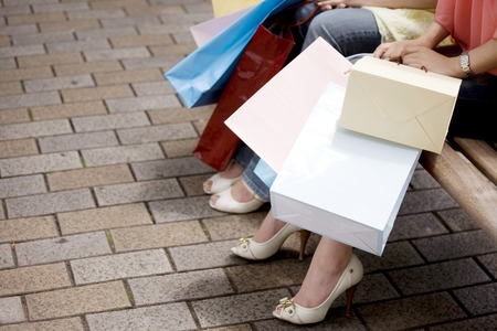shopping buddies: Two women to break sat on a bench Stock Photo