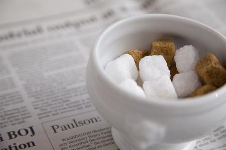 砂糖の立方体および新聞 写真素材