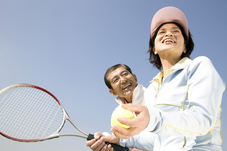 テニスコートを持っているカップル