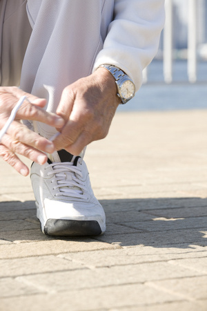 lean over: Hand of the man that connects the shoe laces