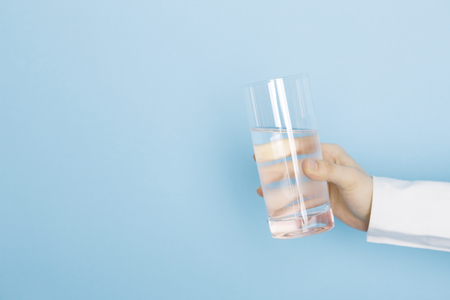Hands of women with containing glass of water