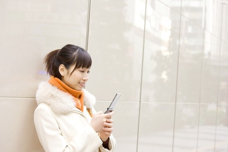 the silencer: Woman looking at the mobile in the city