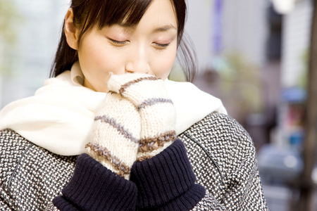 damper: Women warm the hands gloved in the city