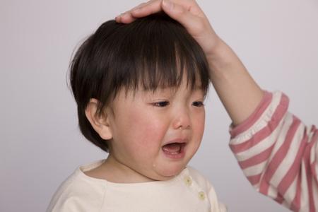 赤ちゃんは、お母さんに頭をなでる頼まれる 写真素材