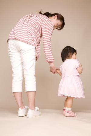 hold ups: Baby walking by connecting the mother and hand