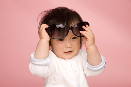 ladies bust: Baby that tries to get sunglasses Stock Photo