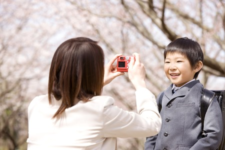 nuclear family: Mother to take the son photo under the cherry tree Stock Photo