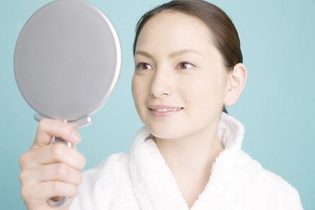 woman mirror: Woman looking in the mirror Stock Photo