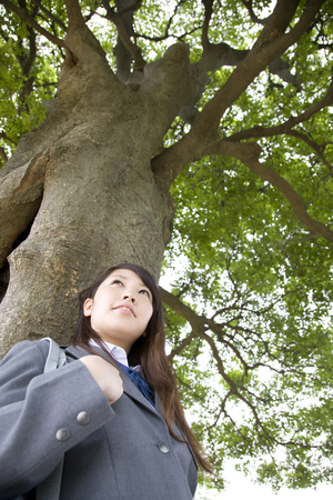 leaning against: High school girl leaning against a tree