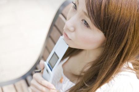 失った女性はあごに携帯電話を適用することによってとベンチに座って 写真素材