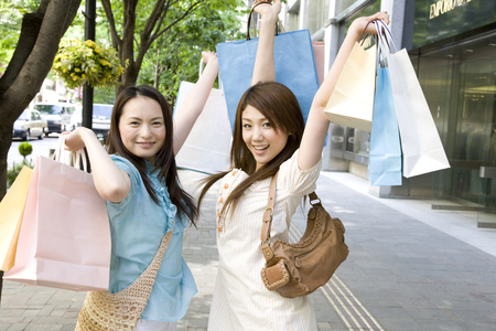 shopping buddies: Frolic 2 females with both hands in a shopping bag in the city Stock Photo