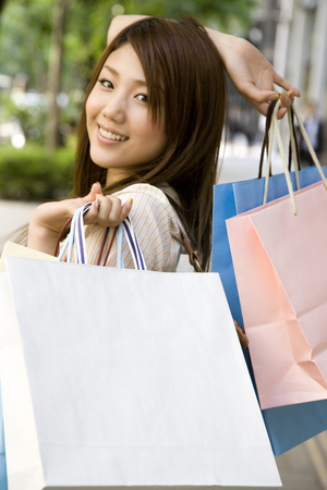 frolic: Frolic woman with both hands in a shopping bag in the city Stock Photo