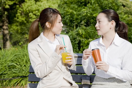 2 women of drinking a drink at one of the park bench