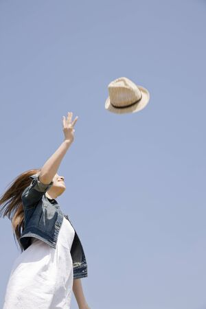 fling: Women fling a hat Stock Photo