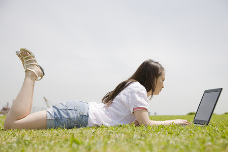 Woman looking at a laptop on the lawn