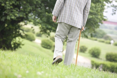 From behind the old man to walk while month cane the park Stock Photo