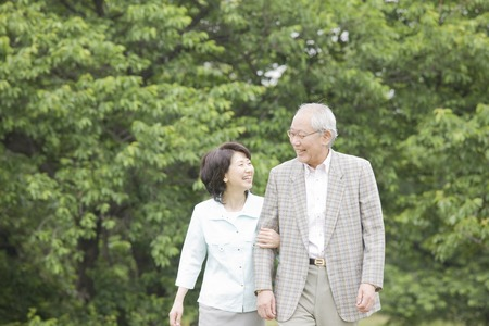 Elderly couple to walk in the park while draw arm