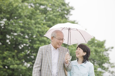 pleasant emotions: Elderly couple for a walk with parasols