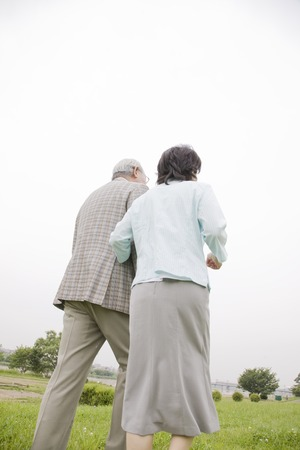 riverbed: Back view of the elderly couple to walk in the riverbed while draw arm Stock Photo