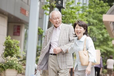 go shopping: Elderly couple walking while draw arm around town Stock Photo