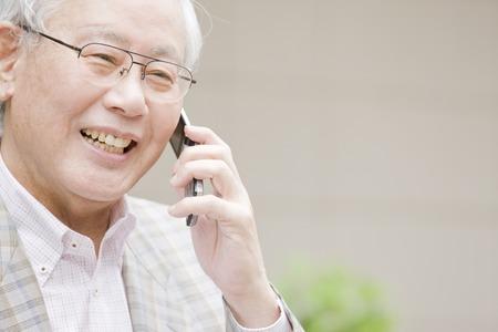 El viejo hombre para llamar por un teléfono móvil Foto de archivo