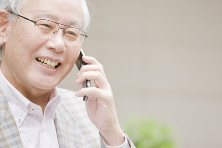 idoso: Old man to call on a mobile phone Banco de Imagens