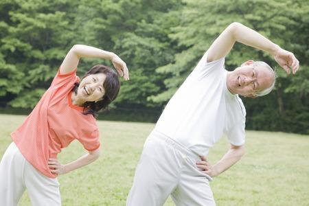公園でラジオ体操する老夫婦