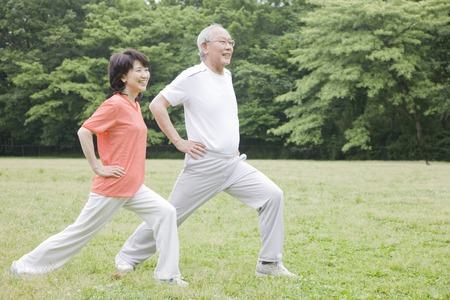 an elderly person: Elderly couple for a stretch in the park