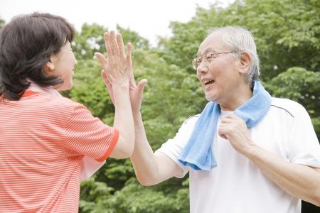 公園でハイタッチする老夫婦