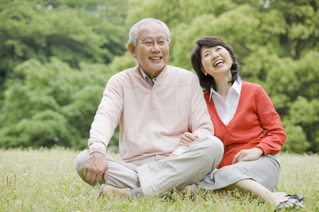 Elderly couple sitting on a conversation on the grass of the park Stock Photo - 49294554