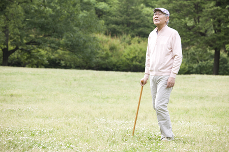 idoso: Old man with a cane to walk in the park Banco de Imagens