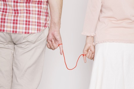 little finger: Hand of an elderly couple wrapped a red thread on little finger
